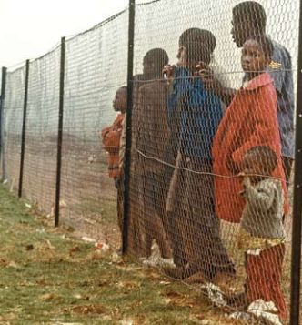 """In this photo of 1973, Frontiers within frontiers: children behind fence that separated them from the white community near Johannesburg. The 'one people' project in South Africa won in part as a conquest of ideas and feelings.</p> <p>Copyright UN/Pendl."""" width=""""332″ height=""""357″ /><strong>In this photo of 1973, Frontiers within frontiers: children behind fence that separated them from the white community near Johannesburg. The 'one people' project in South Africa won in part as a conquest of ideas and feelings.Copyright UN/Pendl.</strong>We can call this 'joined-up thinking'.</p> <p> It reinforces 'joined-up feeling', through a greater awareness of interconnection. Awareness of effects—actual, probable or possible— on others from one's actions may support feelings of sympathy, even responsibility; while awareness of boomerang effects— actual, probable or possible—on oneself can generate feelings of caution and precaution. A perspective of joined-up thinking, in which environmental insecurity, health insecurity, economic insecurity, military insecurity, psychological insecurityand more all sometimes strongly affect each other, reduces the significance of definitional disputes.</p> <p> Broad attention to types of threat and damage fits with a broad causal analysis, but even those users of a narrow physical violence definition of human security, who adopt a transdisciplinary causal perspective, are led to engage with other types of insecurity and harm, and with how people value and react to them.Which of these connections are considered most important remains a matter for investigation and evaluation, caseby-case. Jolly and Basu Ray (2007) show this based on the national Human Development Reports which have taken human security as a theme. A human security perspective is a frame for work, elaborated differently each time, not an instruction to study the effect of everything on everything or a fixed blueprint of research design.</p> <p><h3>Issues In Global Ethics</h3> <"""